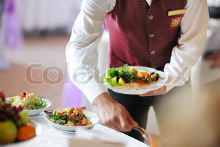 Waiter carrying a plate with meat dish