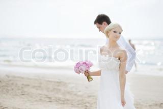Beach wedding: bride and groom by the sea