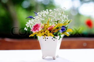 A vase full of assorted flowers outdoors