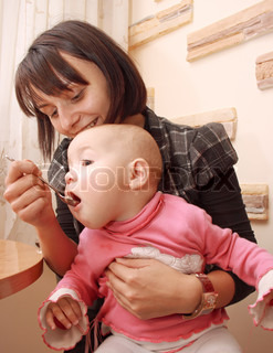 Mother feeds baby spoon