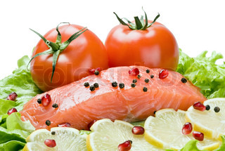 fresh red fish with lemon and vegetables isolated on white background