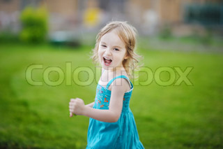 Adorable little girl laughing outdoors