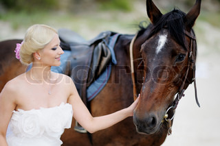 Beach wedding: bride and a horse by the sea