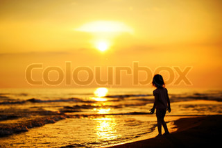 A child as silhouette by the sea