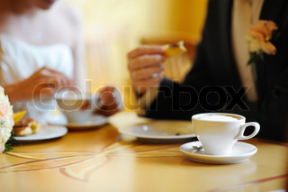Coffee cup on a table bride and groom on a background