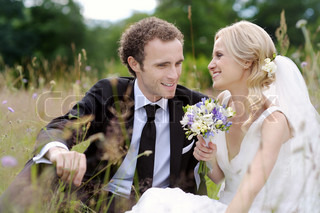 Bride and groom having fun while sitting in a meadow