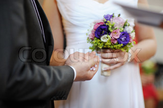 Groom holding bride's hand during the wedding ceremony
