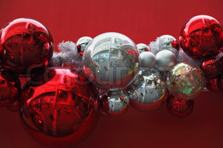 Gorgeous garland of Christmas decorations Bright red and silver glass balls on a red background