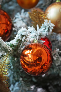 Multi-colored mirrored balls and gold tinsel decorated a Christmas tree