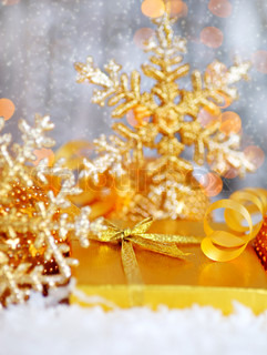 Winter holiday background with golden present gift box, Christmas tree snowflake ornament