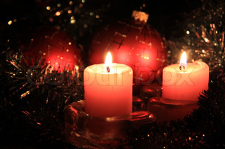 Christmas candles against a tinsel and red spheres