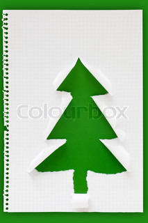 Handmade Christmas tree made of ripped notebook paper on green paperboard background