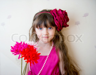 Pretty little girl in beautiful dress with flowers and stylish headband