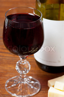 Wine glass and bottle and cheese on a table