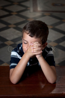 A young boy praying in church with eyes closed