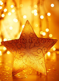 Christmas tree star decoration with winter ornament as holiday background over abstract defocus golden lights