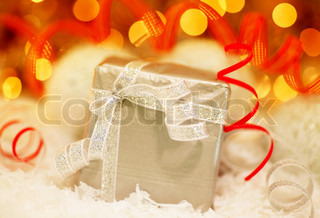 Winter holiday background with silver present gift box, red ribbon ornament & Christmas snow decoration