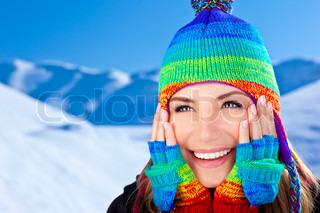 Glad smilende pige iført farverige hat , smukke kvindelige close up portræt , unge smukke kvinde ansigt over sne bjerge blå baggrund , vinter sjovt udendørs, glade mennesker koncept
