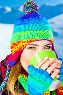 Beautiful girl drinking hot chocolate outdoor in winter, happy female teen wearing colorful hat, young pretty woman face, holding cup in hands