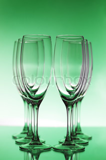 Empty champagne glasses on a green background