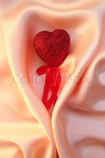 Red heart on elegant pink silk for St Valentine's day background