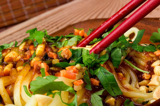 Close-up photograph of red chopsticks on freshly prepared Asian noodles