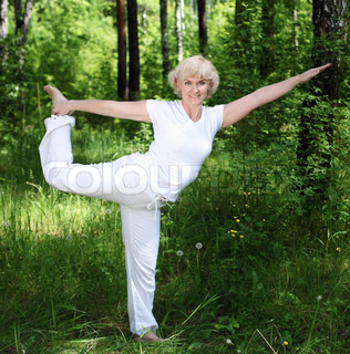 An elderly woman practices yoga in nature The symbol of healthy lifestyle