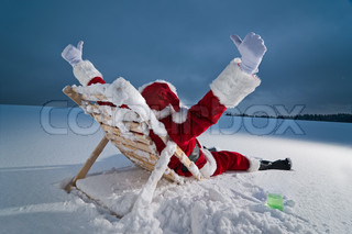 Santa claus relaxing on a sunbed in snow at night