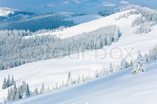 winter calm mountain landscape with sheds group on slope Kukol Mount, Carpathian Mountains, Ukraine