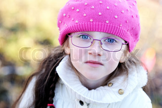 A portrait of little girl in glasses wearing pink cap