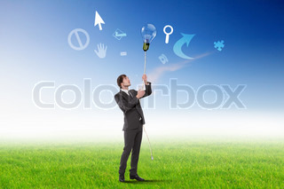 Businessman standing on green grass and thinking creatively
