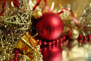 Still life of red and gold Christmas ornaments In the foreground, a small gift