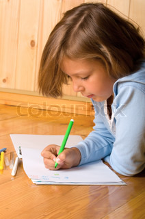 little girl is drawing while laying on the floor