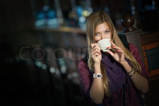 young beautiful woman in a cafe with a cup of coffee
