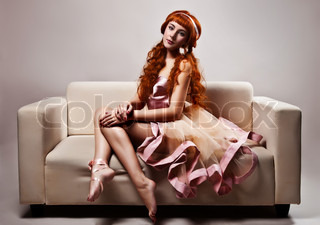 The image of a beautiful woman in luxurious dress sitting on sofa