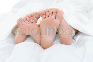 Close-up of the feet of a couple on the bed Isolated on white background