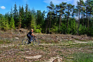 a young boy is cycling off road in the woods