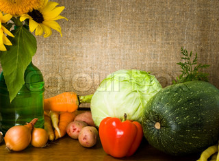 Still life with vegetables and sunflowers in green bottle burlap background, with copy space