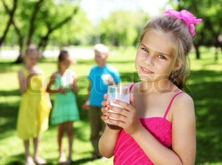 Little girl drinking milk in the summer park