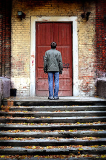 man stand on stairs of an old house with closed door