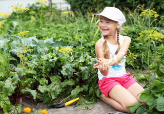 Little happy girl gardening in the summer