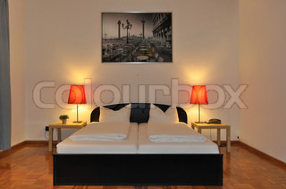 View of a spacious and modern hotel room with double bed and bedside lamps on