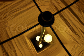 View from above into a paper lamp with 3 burning lightbulbs