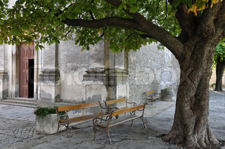 Lonely village scenery: Benches standing close to each other under tree in front of open church door