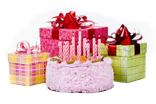 Pie with twelve candles and gifts in boxes on a white background