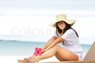 young attractive woman in summer hat relaxing on beach