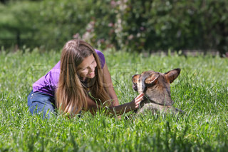 young woman playing with dog in park