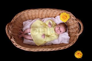 newborn in basket on the black background
