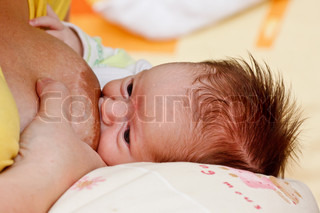 Adorable baby girl sucking at her mother's