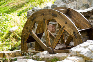 Old watermill with a wooden wheel and stone walls